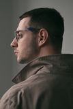 A lonely handsome guy in a raincoat and glasses with different moods. Psychological portrait of a lonely guy wearing glasses, a white shirt and a cloak with a Royalty Free Stock Image