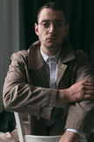 A lonely handsome guy in a raincoat and glasses with different moods. Psychological portrait of a lonely guy wearing glasses, a white shirt and a cloak with a Royalty Free Stock Photos