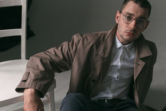 A lonely handsome guy in a raincoat and glasses with different moods. Psychological portrait of a lonely guy wearing glasses, a white shirt and a cloak with a Royalty Free Stock Photo