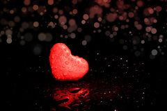 Lonely heart. Red plasticine heart alone on a black bokeh background Royalty Free Stock Photo
