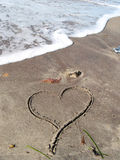 Lonely heart on the beach. A heart written on the sand Royalty Free Stock Photography