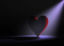 Lonely Heart. A large red heart on a dark background is dramatically lit from behind by a pale purple spotlight Stock Photo