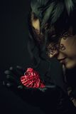 Lonely heart. Old-fashioned young lady in mask holding heart in her hands royalty free stock images