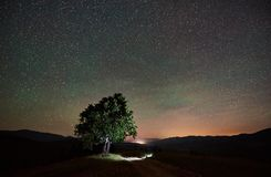 Lonely high tree under starry night sky and Milky way. Illuminated lonely high tree under amazing starry night sky and Milky way in the mountains royalty free stock photo