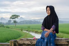 Lonely hijab girl with her smile in the river and field royalty free stock image
