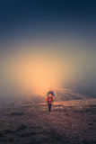 Lonely hiker  with backpack walking along the trail on the mountain top at foggy day time. Royalty Free Stock Images