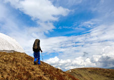 Lonely hiker with blue sky. Male trekker walks along a mountain path, in background the blue sky Stock Image