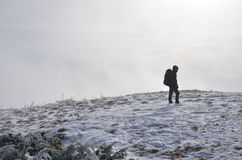 Lonely hiker. One hiker standing on a mountain slope covered by snow in hazy atmosphere Royalty Free Stock Photography