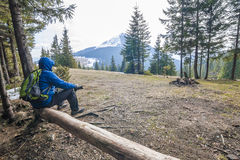 Lonely hiker traveler sitting on a log waching mountain scenery Stock Photography