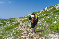 Lonely hiker walks through Chatyr-Dah mountainous massif in Crimean mountains Royalty Free Stock Images