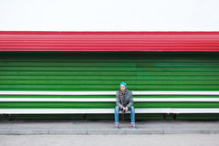 Lonely hipster male sitting on a bench Royalty Free Stock Photo