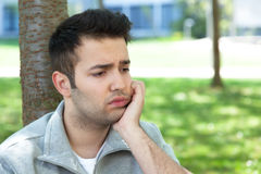 Lonely hispanic man outside in a park. Lonely hispanic man with short black hair outside in a park looking sad Stock Images