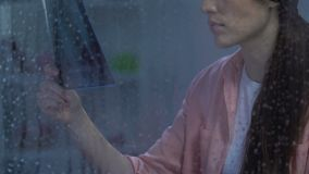 Lonely hopeless sick lady looking at lungs x-ray near rainy window, cancer stage. Stock footage stock footage