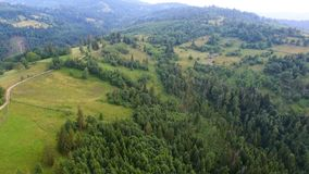 Aerial shot lonely house in countryside on green meadow near forest in mountains stock video footage