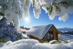 Lonely house covered with snow on top of the mountain. Lonely house covered with snow standing near the forest on top of the mountain in sunny day Stock Photo