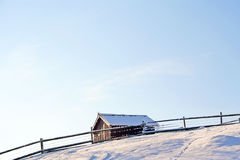 Lonely house in mountains under sky. Lonely wooden house beyond wooden fence in snow-covered mountains under blue sky Stock Images
