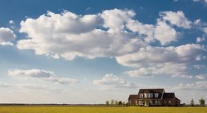 Lonely House On The Prairie. Solitary lonely  house sits by itself on large field with blue sky and clouds Royalty Free Stock Image