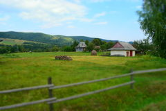 Lonely houses in the fields. Lonely houses behind a wooden fence in the fields with toy effect. Firewood and a haystack in the yard. Somewhere in Western Ukraine Stock Photos