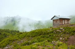Lonely Hut in the Green Mountains with Morning Autumnal Fog Stock Photo