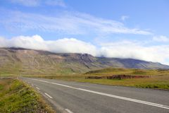Lonely Iceland Road. Lonely road in front of an impressive mountain scenery with paddocks and a farm under thick cloud layers wallowing over the mountain rim Royalty Free Stock Images