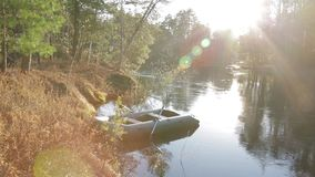 A lonely inflatable boat near the shore. Of a wild taiga river. Sunset,a warm summer evening stock video footage
