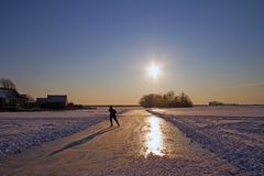 Lonely isce skating in the countryside from the Netherlands in w. Inter at sunset Royalty Free Stock Photo
