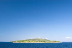 Lonely island. Lonely mediterranean green island against blue sky stock images