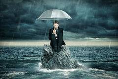 Lonely Island. Man with umbrella sitting on Lonely Island Stock Images