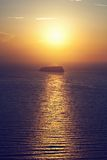 A lonely island, rock on the sea at sunset Stock Image