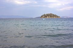 Lonely island in a sea. Mediterranean Sea and Mountains in Tolo, Peloponnese Stock Photo