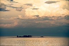 Lonely Island. With strong, cloudy and orange sky Stock Images