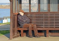Lonely isolated man on coastal bench Royalty Free Stock Photography