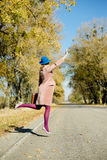 Lonely lady in bowler hat holding retro suitcase. Lonely lady in blue bowler hat and beige overcoat holding retro suitcase hitchhiking, jumping high on a sunny Stock Image