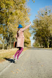 Lonely lady in bowler hat holding retro suitcase. Lonely lady in blue bowler hat and beige overcoat holding retro suitcase hitchhiking, jumping high on a sunny Stock Images
