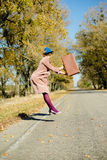 Lonely lady in bowler hat holding retro suitcase. Lonely lady in blue bowler hat and beige overcoat holding retro suitcase hitchhiking, jumping high on a sunny Royalty Free Stock Image