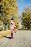 Lonely lady in bowler hat holding retro suitcase. Lonely lady in blue bowler hat and beige overcoat holding retro suitcase hitchhiking on a sunny day in autumn Royalty Free Stock Photo