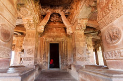 Lonely lady sitting at entrance of traditional Hindu temple with stone wall relief of 7th century, India. Stock Images