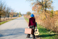 Lonely lady walking away with retro suitcase and Royalty Free Stock Images