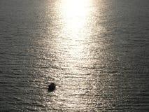 So lonely in life and ocean. Sunlight on water. Sunlight on the sea in a grey evening. Luz del sol sobre el mar en una tarde gris. ship, sun, reflect, water royalty free stock photo