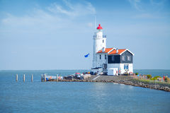 Lonely lighthouse stands on the spit in the sea near the village Royalty Free Stock Photo