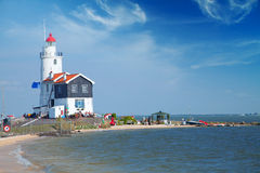 Lonely lighthouse stands on the spit in the sea near the village Stock Photos