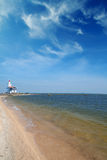 Lonely lighthouse stands on the spit in the sea near the village Stock Photo