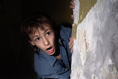 Lonely little boy in a dark cellar Royalty Free Stock Images