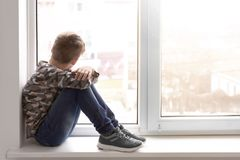 Lonely little boy near window indoors. Child autism royalty free stock photo