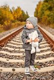 A lonely little boy in old-fashioned gray clothes hugs a bunny in the middle of the forest on abandoned railway rails Royalty Free Stock Images