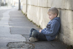 Lonely little boy sits at pathyway. Young child sits alone at sidewalk Royalty Free Stock Image