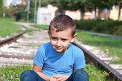 Lonely little boy sitting on a rails Stock Images