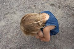 Lonely little girl. Sadly sitting on the ground Stock Photography