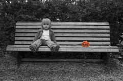 Lonely little girl with flowers sitting on the bench Royalty Free Stock Images