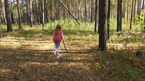 A lonely little girl lost her way in the autumn forest. A girl wanders with a wooden stick. A lonely little girl lost her way in the autumn forest. A girl stock video footage